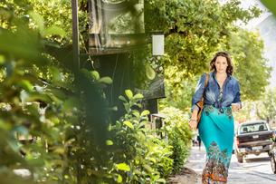 Woman walking on roadside with takeaway coffee, Franschhoek, South Africaの写真素材 [FYI03549133]