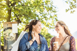 Two women friends with takeaway coffee chatting in park, Franschhoek, South Africaの写真素材 [FYI03549136]