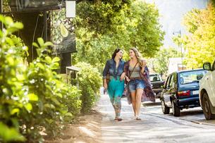 Two female friends strolling on roadside  arm in arm, Franschhoek, South Africaの写真素材 [FYI03549138]