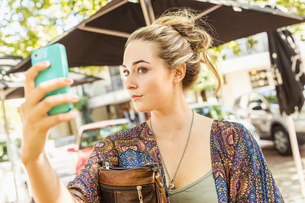 Young woman checking herself on smartphone at sidewalk cafe, Franschhoek, South Africaの写真素材 [FYI03549148]