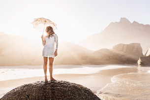 Woman standing on rock with parasol on sunlit beach, Cape Town, South Africaの写真素材 [FYI03549163]
