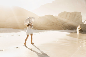 Rear view of woman strolling with parasol on sunlit beach, Cape Town, South Africaの写真素材 [FYI03549165]