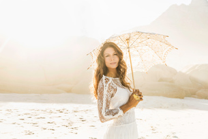 Portrait of beautiful woman holding parasol on sunlit beach, Cape Town, South Africaの写真素材 [FYI03549166]
