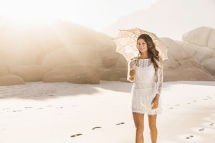 Beautiful woman strolling with parasol on sunlit beach, Cape Town, South Africaの写真素材 [FYI03549167]