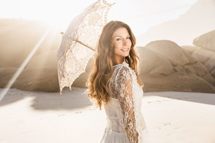 Portrait of beautiful woman holding parasol looking over her shoulder on sunlit beach, Cape Town, Soの写真素材 [FYI03549168]