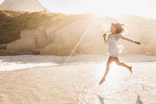 Woman jumping mid air with parasol on sunlit beach, Cape Town, South Africaの写真素材 [FYI03549170]