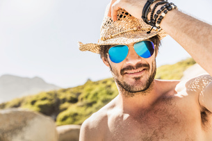 Portrait of man wearing blue mirrored sunglasses and straw hat on beach, Cape Town, South Africaの写真素材 [FYI03549251]