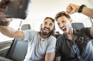 Friends in back seat of car taking selfieの写真素材 [FYI03549265]