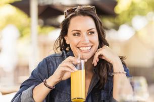 Woman at sidewalk cafe drinking orange juice looking away smilingの写真素材 [FYI03549286]
