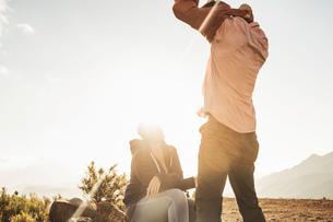 Man in field removing jumperの写真素材 [FYI03549314]