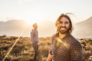 Man and friend on grassland looking at camera smilingの写真素材 [FYI03549339]