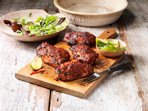 Food, deli chicken carolina thighs, wooden chopping board, fresh lime and chilli, salad in wooden boの写真素材 [FYI03549407]
