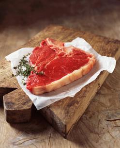Food, meat, beef, t-bone steak, on rustic wooden chopping boardの写真素材 [FYI03549429]