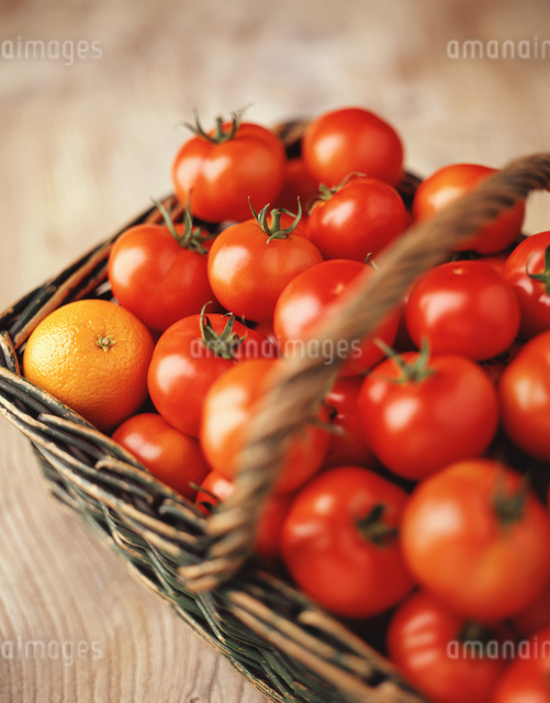 Food, fruit and vegetables, fresh vine tomatoes and an orange in a wicker basketの写真素材 [FYI03549460]