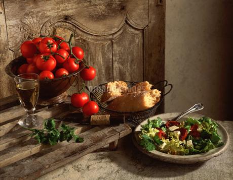 Traditional display of mediterranean food, on the vine tomatoes, crusty white ciabatta bread, saladの写真素材 [FYI03549488]