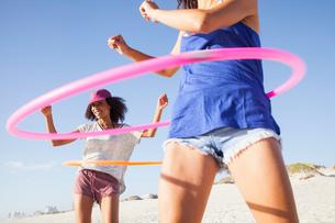 Women on beach using hula hoopsの写真素材 [FYI03549550]