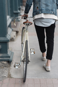 Young man walking with bike, rear view, low sectionの写真素材 [FYI03549589]