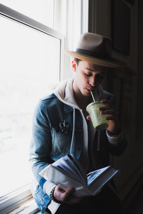 Young man at home, sitting on windowsill, drinking health drink, reading bookの写真素材 [FYI03549601]