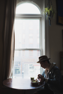 Young man sitting at table by window, eating healthy mealの写真素材 [FYI03549604]