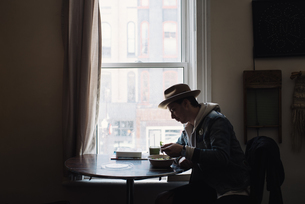 Young man sitting at table by window, eating healthy mealの写真素材 [FYI03549605]