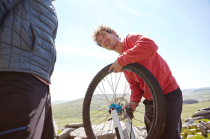 Cyclists repairing bicycle on mountainsideの写真素材 [FYI03549683]