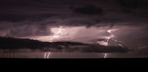 Two cloud-to-ground lightning bolts shoot through the low clouds of a supercellの写真素材 [FYI03549734]
