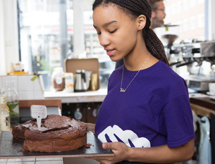 Waitress removing chocolate cake from cafe counterの写真素材 [FYI03549960]