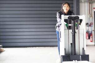 Technician moving machine in factoryの写真素材 [FYI03550116]