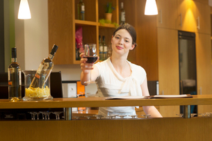 Bartender in wine bar holding wine glass looking at camera smilingの写真素材 [FYI03550144]