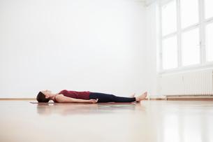 Woman in exercise studio lying on back on floorの写真素材 [FYI03550245]