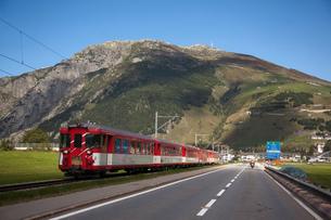 Train running parallel to road, Gotthard Pass, Ticino, Switzerlandの写真素材 [FYI03550499]