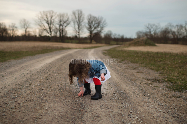 Young girl picking up stone from dirt pathの写真素材 [FYI03550737]