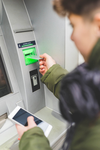 Young woman using cash machine, rear viewの写真素材 [FYI03550815]