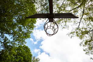 Low angle view of basketball hoop silhouetted against blue skyの写真素材 [FYI03550892]