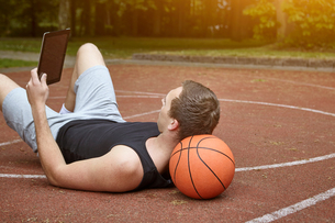 Young male basketball player lying on court browsing digital tabletの写真素材 [FYI03550902]