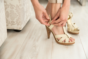 Detail of young woman fastening high heel sandalsの写真素材 [FYI03550972]