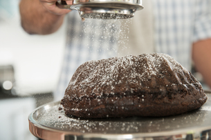 Man sieving icing sugar over cakeの写真素材 [FYI03550999]