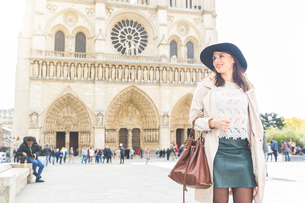 Stylish young woman strolling in front of Notre Dame, Paris, Franceの写真素材 [FYI03551064]