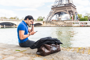 Young man sitting beside river, looking at smartphone, Eiffel Tower in backgroundの写真素材 [FYI03551179]