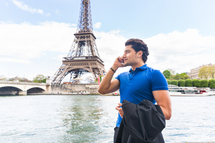 Young man walking beside river, using smartphone, Eiffel Tower in backgroundの写真素材 [FYI03551180]