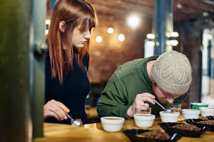 Coffee shop team smelling bowls of coffee and coffee beans at tastingの写真素材 [FYI03551214]
