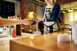 Female barista taking smartphone contactless payment from coffee shop customerの写真素材 [FYI03551245]