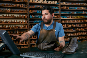 Male cobbler making invoice for boots in traditional shoe shopの写真素材 [FYI03551478]