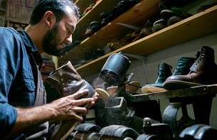 Male cobbler in traditional shoe workshop repairing boot heelの写真素材 [FYI03551496]