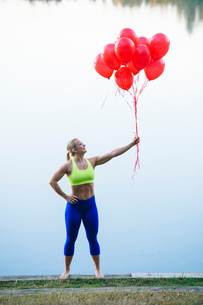 Woman holding bunch of red balloonsの写真素材 [FYI03551499]