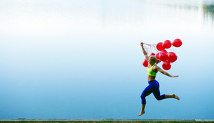 Woman holding bunch of red balloons jumping in mid airの写真素材 [FYI03551500]