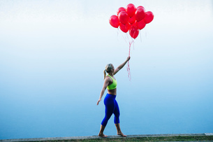 Side view of woman holding bunch of red balloonsの写真素材 [FYI03551501]