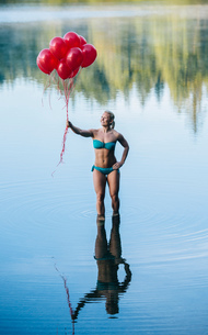 Woman ankle deep in water holding bunch of red balloonsの写真素材 [FYI03551502]