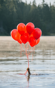 Hand in water holding bunch of red balloonsの写真素材 [FYI03551504]