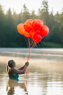 Woman in water holding bunch of red balloonsの写真素材 [FYI03551505]